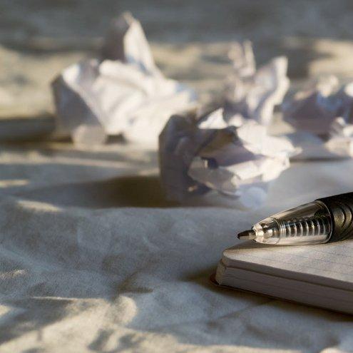 Bolígrafo, cuaderno y papeles arrugados. Bloqueo del escritor